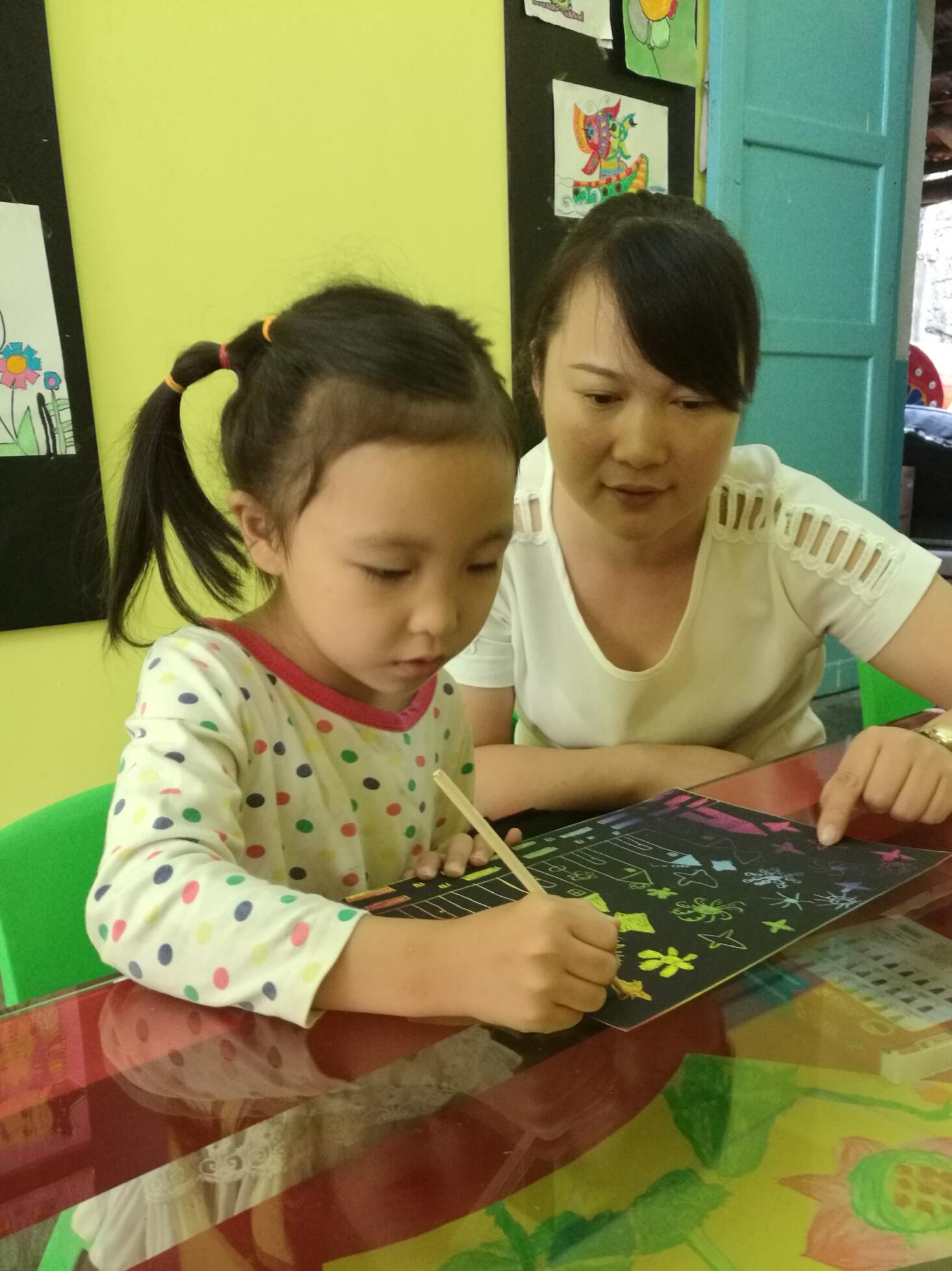 图一、罗老师看着宝贝正在画天上的星星